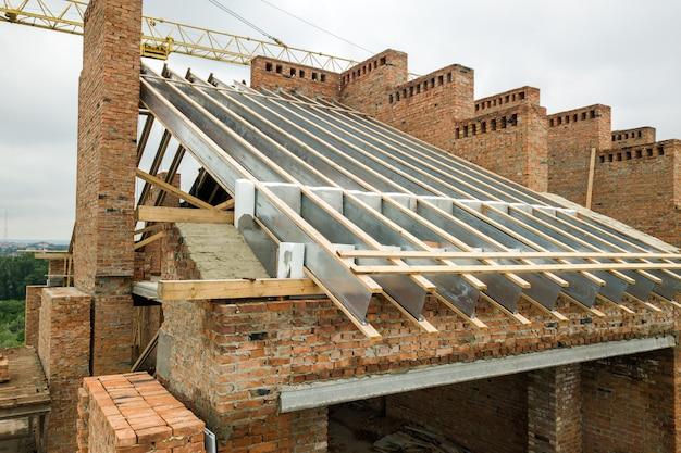Budynek mieszkalny murowany w stanie surowym z drewnianą konstrukcją dachu w trakcie budowy.
