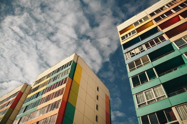 Budynek mieszkalny na tle nieba. kolorowa fasada nowoczesnej zabudowy mieszkaniowej z balkonami.