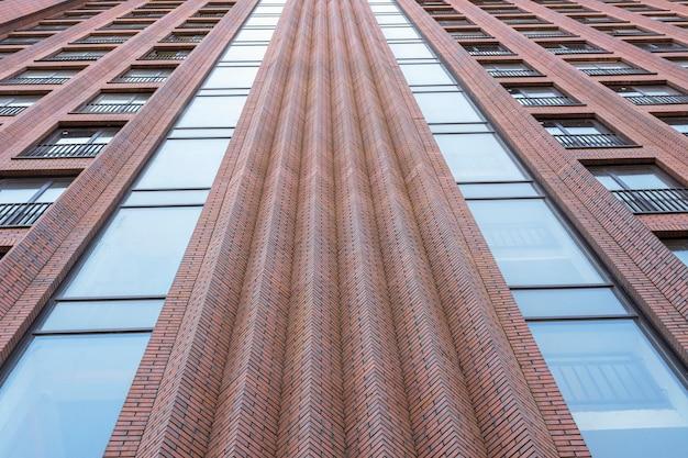 Budynek mieszkalny w stylu loft. duże okna w czerwonej ścianie z cegły.