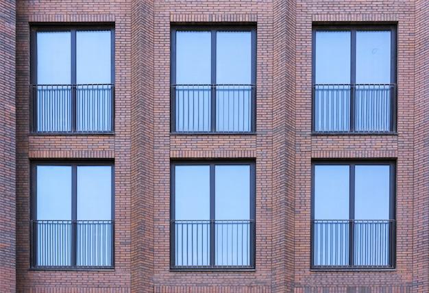 Budynek mieszkalny w stylu loftu. duże okna w ścianie z czerwonej cegły.