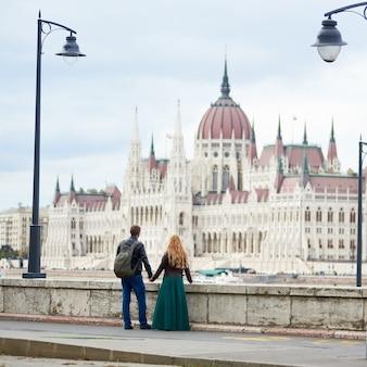 Budynek parlamentu w budapeszcie, węgry. widok z tyłu pary turystów trzymających się za ręce i cieszących się widokiem wspaniałej architektury budapesztu między dwiema starożytnymi latarniami