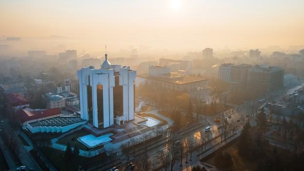 Budynek prezydencji o wschodzie słońca w kiszyniowie w mołdawii. mgła w powietrzu, nagie drzewa, budynki, drogi.