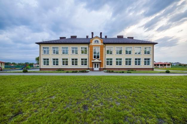 Budynek przedszkola z dużymi oknami na zielonym trawiastym trawniku