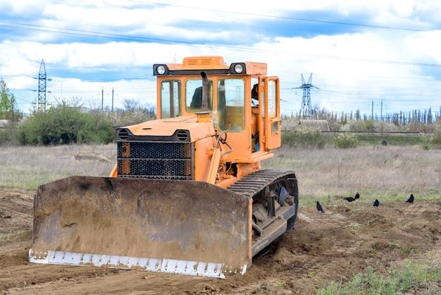 Budynek przemysłowy spychacz terenu niwelacja i przenoszenie gleby podczas budowy autostrady. żółty buldożer na gliniastym placu budowy