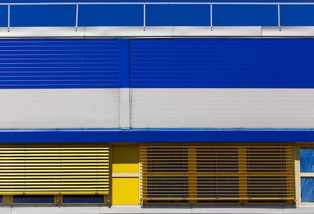 Budynek przemysłowy z niebieskim i żółtym metalowym wykończeniem bocznicy. abstrakcyjne tło.