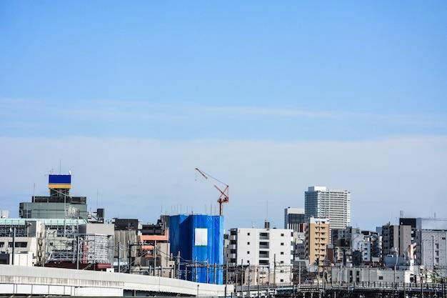 Budynek w budowie w centrum tokio z pejzażem miejskim i niebieskim niebem w tle