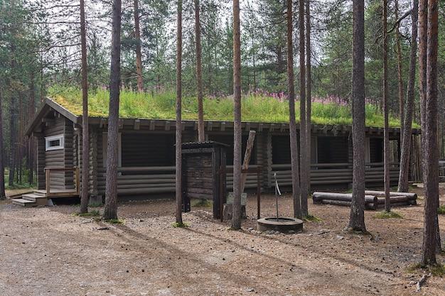 Budynek z bali z dachem z trawy w obozie w lesie