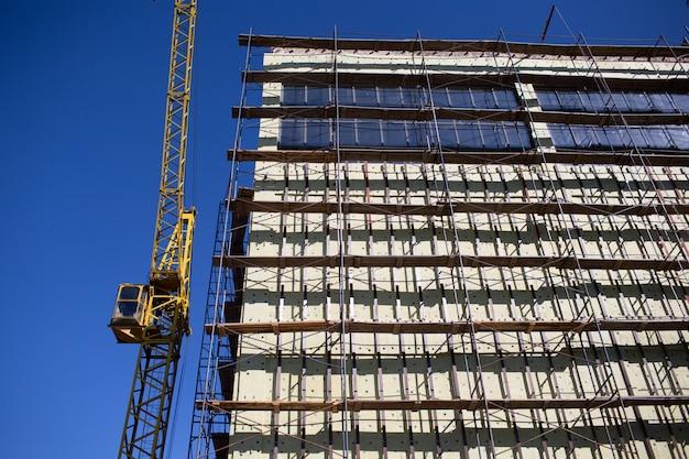 Budynek z dźwigiem budowlanym i niebieskim niebem rusztowania