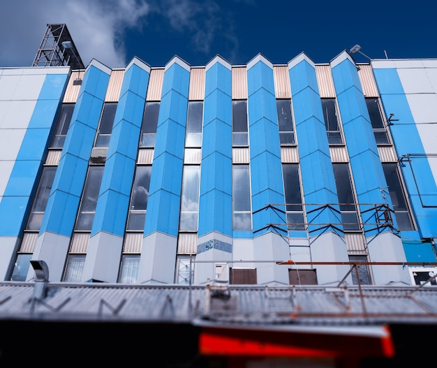 Budynek z pionowymi niebieskimi kolumnami okiennymi w tle miasta