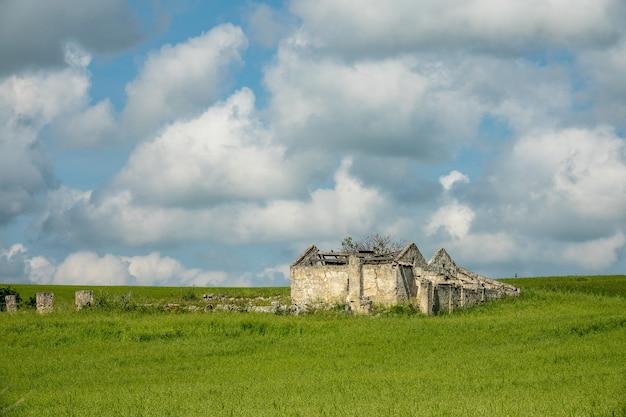 Budynek zbudowany na zielonym polu pod niebem pełnym chmur w ciągu dnia