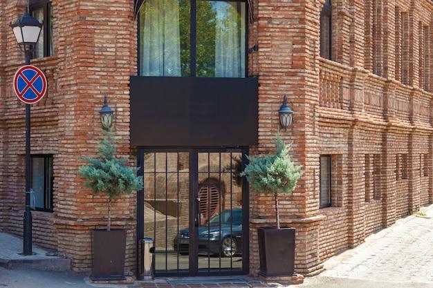 Budynek ze starej czerwonej cegły z szyldem duże okna i kwiaty w doniczkach przy drzwiach