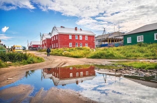 Budynki mieszkalne koloru czerwonego na wyspach sołowieckich i odbicia w kałuży pod błękitnym niebem