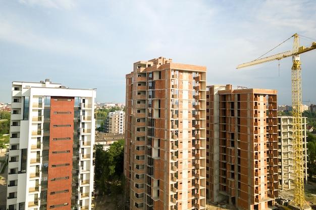 Budynki mieszkalne wysokościowe i żuraw wieżowy w trakcie realizacji na terenie budowy. rozwój nieruchomości.
