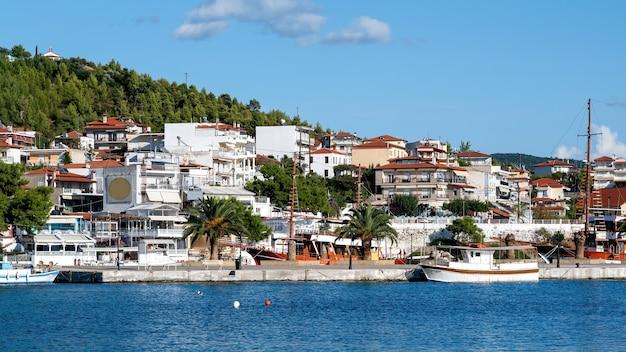 Budynki położone na wzgórzu z mnóstwem zieleni, molo z przycumowanymi łodziami na pierwszym planie, neos marmaras, grecja