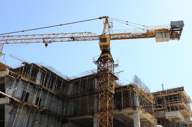 Budynki w budowie i żurawie pod niebieskim niebem