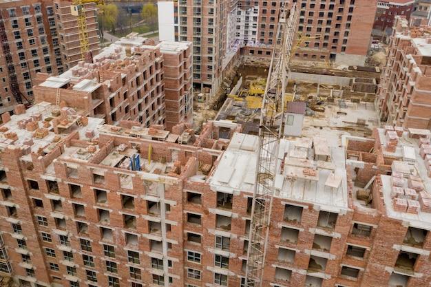 Budynki wielopiętrowe w budowie. żurawie wieżowe w pobliżu budynku. aktywność, architektura, proces rozwoju.