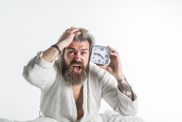 Budzący się późny termin człowiek z budzikiem brodaty mężczyzna w łóżku rano rano rutyna budzik