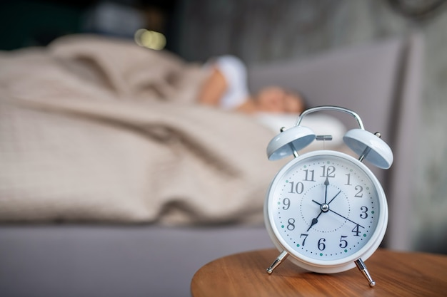 Budzenie się. biały mechaniczny budzik stojący koło łóżka