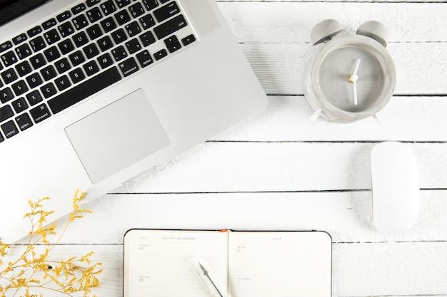 Budzik blisko notatnika i laptopu
