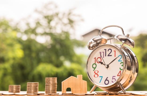Budzik, drewniany dom model i krok monet sterty, natury tło, pieniądze, oszczędzanie, inwestycja lub planowania rodziny pojęcie