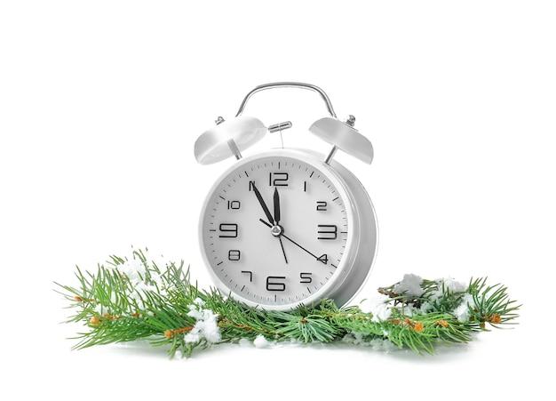 Budzik, gałęzie jodły i śnieg na białym tle. koncepcja odliczania świąt bożego narodzenia