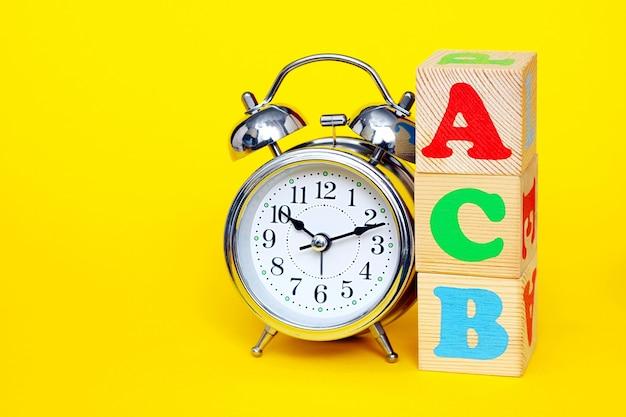 Budzik i czerwone a, zielone c i niebieskie b na drewnianym pudełku z kostką na żółtym tle