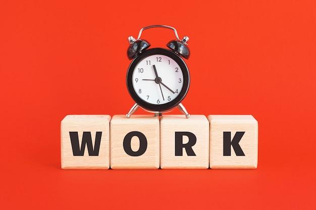 Budzik i drewniane klocki z tekstem praca na jasnym czerwonym tle. biznes, kariera, strata czasu, koncepcja kunktatorstwa.