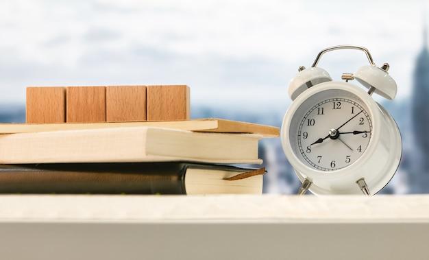 Budzik i drewniane kostki na książkach na stole