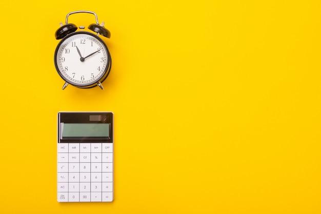 Budzik i kalkulator leżą na białym tle