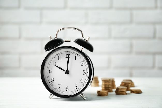 Budzik i monety na białym stole na tle ceglanego muru