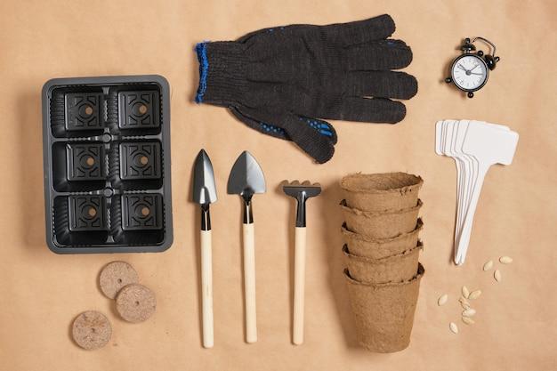 Budzik i narzędzia ogrodowe na papierze pakowym widok z góry, małe szpatułki, rękawiczki i tabletki torfu, wszystko do sadzenia sadzonek