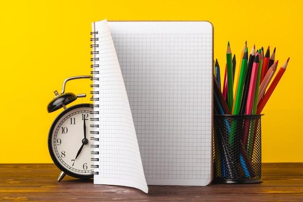 Budzik i notatnik na biurku. powrót do koncepcji szkoły
