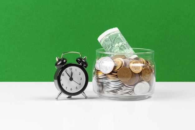 Budzik i pieniądze monety na stole.
