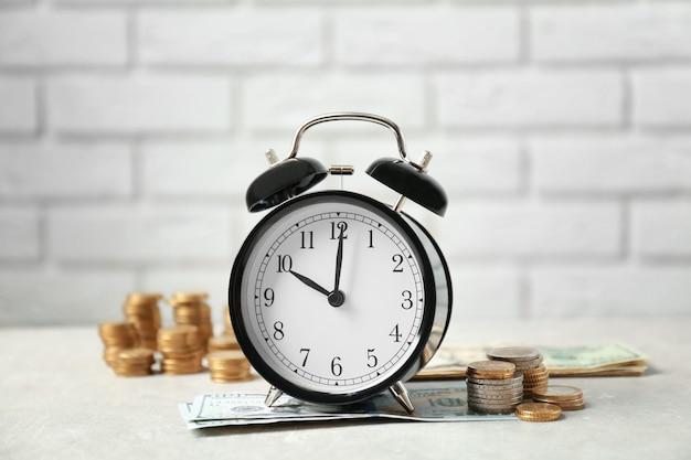 Budzik i pieniądze na białym stole na tle ceglanego muru
