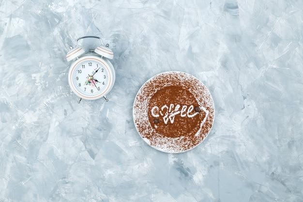 Budzik i płyta z słowo kawy na szarym tle nieczysty