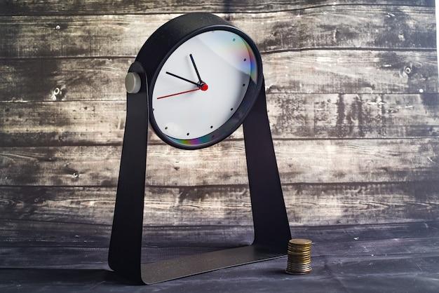 Budzik i stosy monet na drewnianym stole. biznes, finanse, czas, zakupy online, koncepcja oszczędzania pieniędzy.