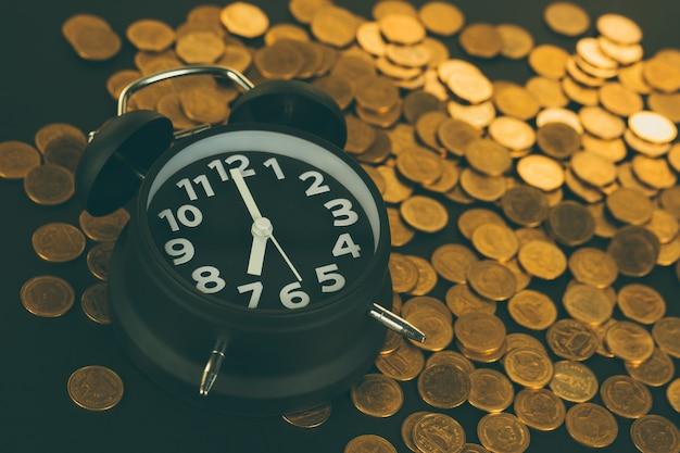 Budzik i stosy monet na stole roboczym