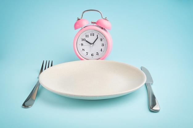 Budzik i talerz ze sztućcami. koncepcja okresowego postu, lunchu, diety i utraty wagi