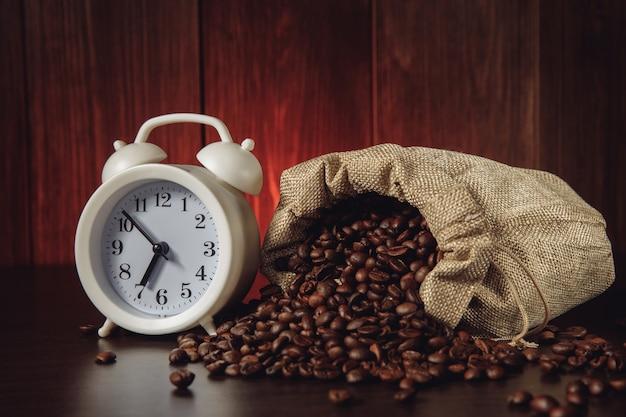 Budzik i ziarna kawy w woreczku.