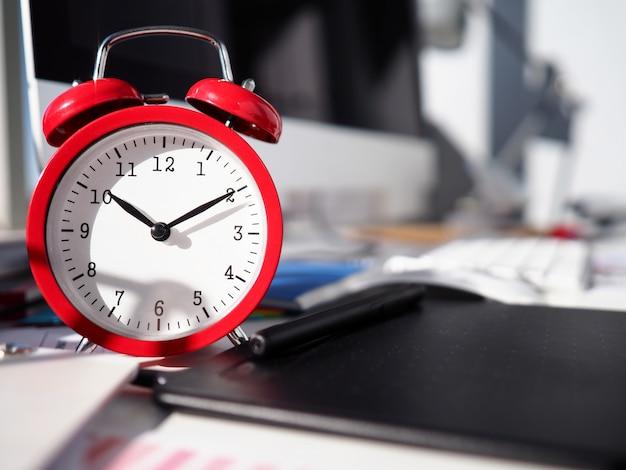 Budzik jest na pulpicie, z bliska tarczą zegarka. optymalne zasoby alokacji do osiągnięcia celów. terminy proces zarządzania czasem. planowanie taktyczne i strategiczne. regularne przypomnienie timera