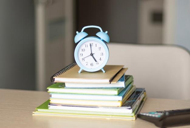 Budzik, książki na stole. koncepcja zarządzania czasem