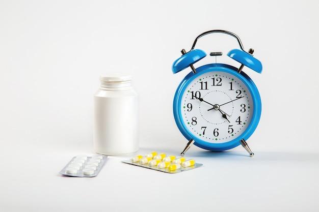 Budzik na białej ścianie pokazuje godzinę przyjmowania leków, a obok nich tabletki medyczne.
