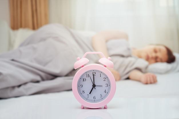 Budzik na niewyraźnym tle śpiącej kobiety w łóżku z miejscem na kopię