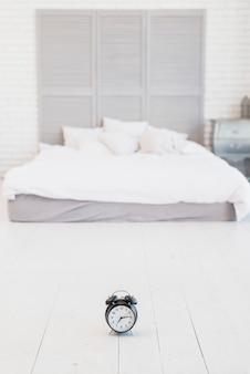 Budzik na podłodze w pobliżu łóżka z białą pościelą