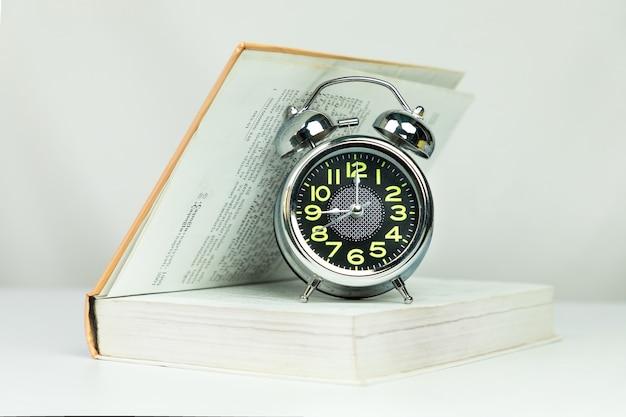 Budzik na pół otwartej książki na białym tle