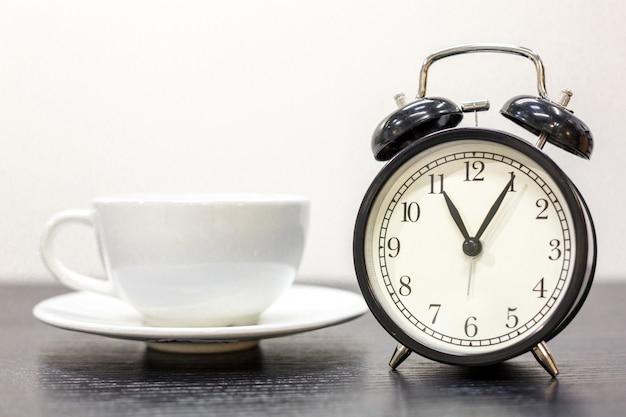 Budzik na stole i biały kubek, czas na herbatę, koncepcja odpoczynku