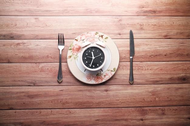 Budzik na talerzu na drewnianym stole, odgórny widok.