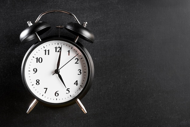 Budzik pokazujący 5'o zegar na czarnym tle