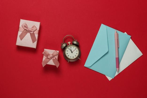 Budzik retro, koperta z listem mikołaja, pudełka z kokardą na czerwonym tle. 11:55. nowy rok, koncepcja bożego narodzenia. widok z góry