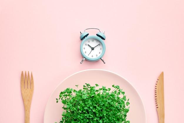 Budzik, sztućce i talerz z zielenią. kolor różowy. koncepcja okresowego postu, pory obiadowej i diety.